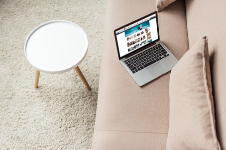 high angle view of laptop standing on cozy couch with amazon website on screen