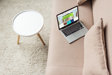 high angle view of laptop standing on cozy couch with bbc website on screen 新聞圖片