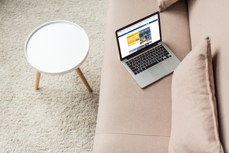 high angle view of laptop standing on cozy couch with booking website on screen 新聞圖片
