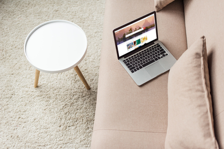 high angle view of laptop standing on cozy couch with shutterstock homepage website on screen 新聞圖片