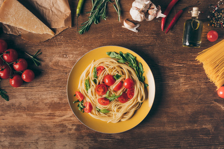 top view of traditional italian pasta with tomatoes and arugula in plate on wooden table with ingredients 写真素材