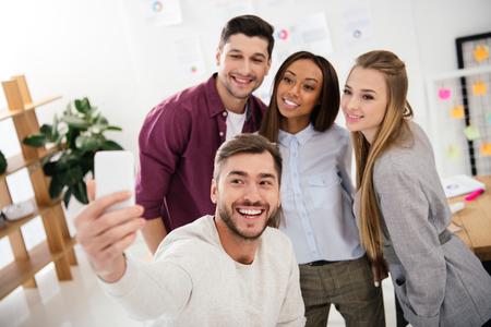 happy multicultural business people taking selfie on smartphone together in office