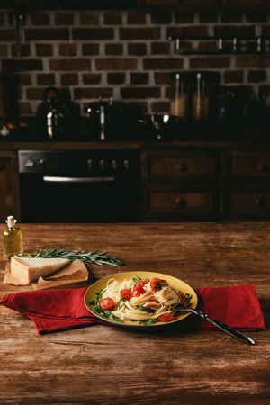 traditional italian pasta with tomatoes and arugula in plate on table with Parmesan and rosemary