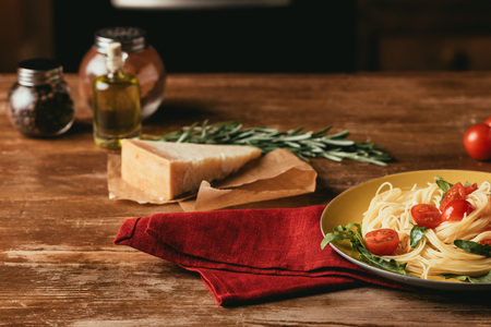traditional italian pasta with tomatoes and arugula in plate on wooden table with Parmesan, rosemary and oil Imagens - 114405348