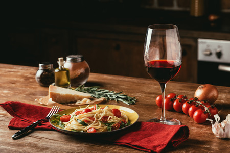 traditional italian pasta with tomatoes and arugula in plate and glass of red wine Standard-Bild