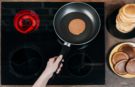 cropped shot of woman frying delicious chocolate pancakes