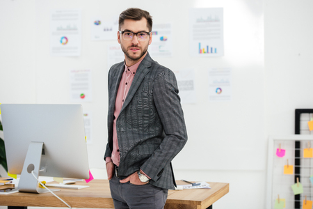 portrait of young businessman in suit and eyeglasses looking at camera at workplace in office Imagens