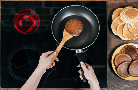 cropped shot of woman flipping pancake on frying pan with wooden spatula
