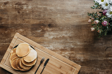 top view of plate full of pancakes on wooden table with flowers bouquet