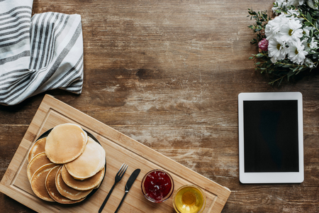 top view of breakfast with pancakes and digital tablet on wooden table Stock Photo