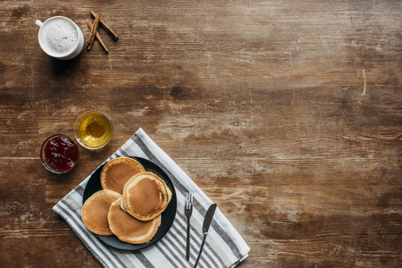 top view of pancakes on striped napking and coffee cup on wooden table Reklamní fotografie