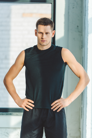 portrait of young sportsman akimbo in sportswear standing in gym Stock Photo