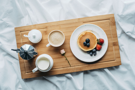 top view of breakfast in bed with freshly baked pancakes and coffee on wooden tray Stock Photo
