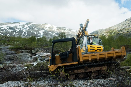 Yellow digger working on a road construction in mountain Norway