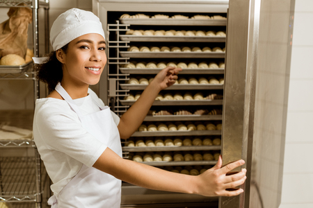 smiling female baker pointing at dough inside of industrial oven at baking manufacture Foto de archivo - 114406203