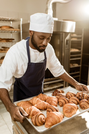 baker holding tray with croissants on baking manufacture 免版税图像