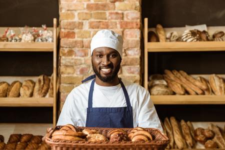 Sonriente panadero afroamericano sosteniendo la cesta con pastelería dulce