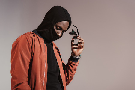 Stylish young african american man wearing hood with face mask and taking of his sunglasses isolated on light background Stockfoto