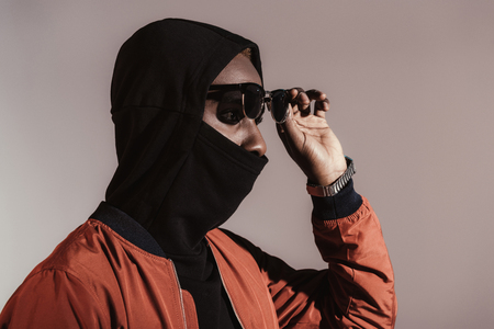 Stylish young african american man wearing hood with face mask isolated on light background