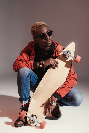 young fashionable african american skateboarder sitting and holding longboard