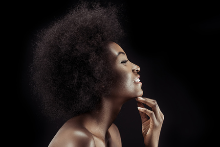 side view of smiling beautiful african american woman isolated on black Stock Photo