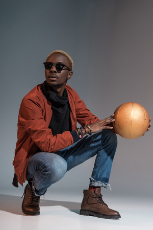 Stylish young african american man sitting with basketball ball in hands Stockfoto - 114406400
