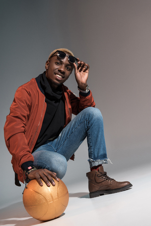 Stylish young african american smiling man holding basketball ball on floor Stockfoto - 114406406