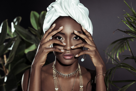 young african american woman in white wire head wrap behind leaves looking at camera through fingers Foto de archivo