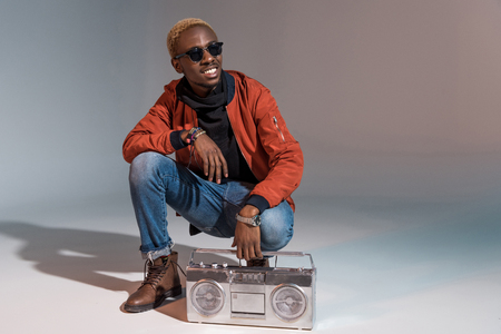 cheerful stylish young african american man crouching with silver tape recorder on grey
