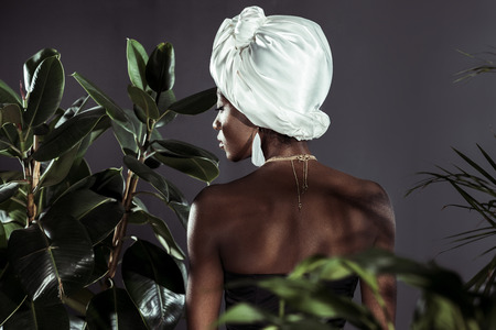rear view of sensual young african american woman in white wire head wrap behind leaves