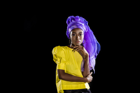 attractive young african american woman in stylish retro clothing isolated on black