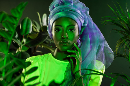 attractive african american woman in traditional wire head wrap under green light behind leaves