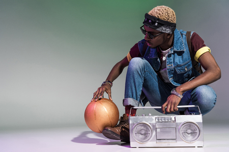 young african american man crouching with golden basketball ball and silver tape recorder on grey 写真素材
