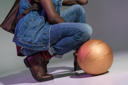cropped shot of african american man crouching with golden basketball ball on grey