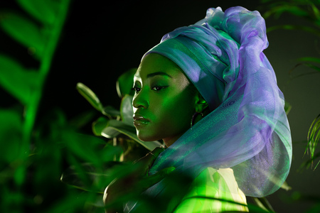 attractive african american woman in wire head wrap under green light behind leaves 免版税图像