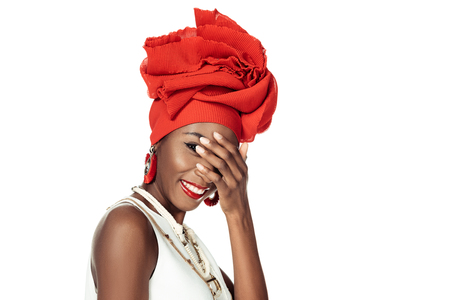 young african american woman in wire head wrap covering face with hand isolated on white Reklamní fotografie
