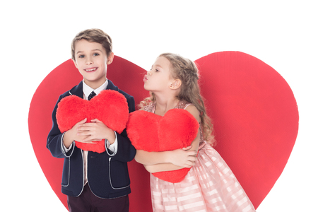 cute little kids holding heart shaped pillows and able to kiss isolated on white