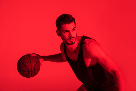 focused young sportsman playing basketball and looking away at contrast red light