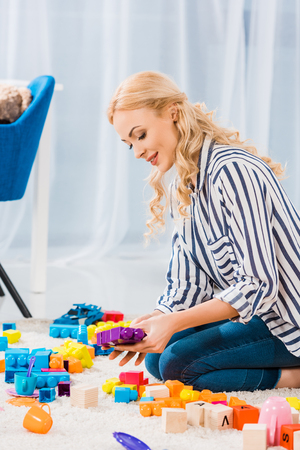 Side view of young mother with toys sitting on floor at home Banco de Imagens