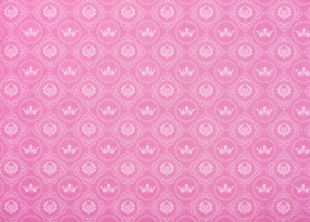set of crowns and ornaments in circles on pink