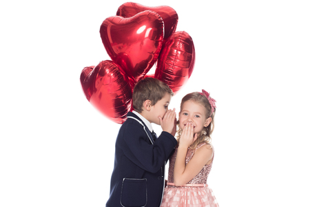 stylish little boy holding heart shaped balloons and whispering to smiling beautiful little girl isolated on white Stock Photo