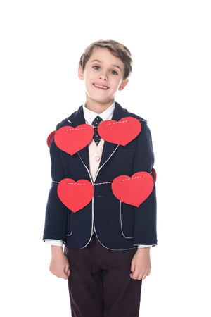 cute little boy in suit staying tied with rope and red hearts, smiling at camera isolated on white 免版税图像