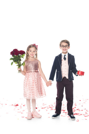 adorable happy kids with roses and heart shaped gift box holding hands and smiling at camera on white