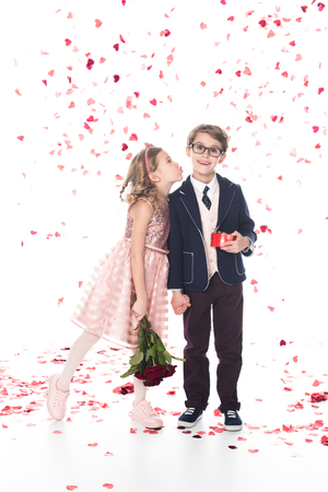 cute little boy in eyeglasses and suit holding gift box and smiling at camera while girl with roses able to kiss him on white with falling heart shaped confetti