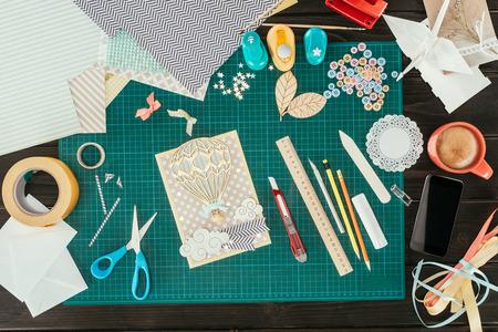 Vista dall'alto del posto di lavoro del designer con modello di cartolina scrapbooking
