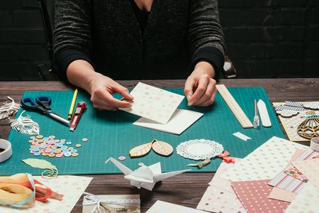 cropped image of designer sitting at table and making scrapbooking postcard