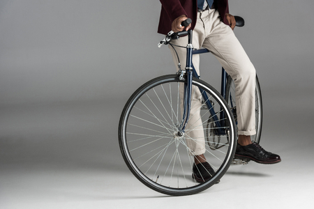 Low section of man siting on bike on grey background Stock Photo