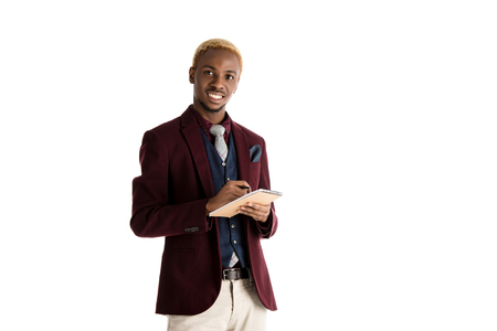 smiling african american man holding notepan and pen in hands isolated on white