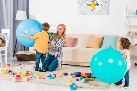 happy mother and kids playing with fitness balls and colorful blocks at home Stock Photo