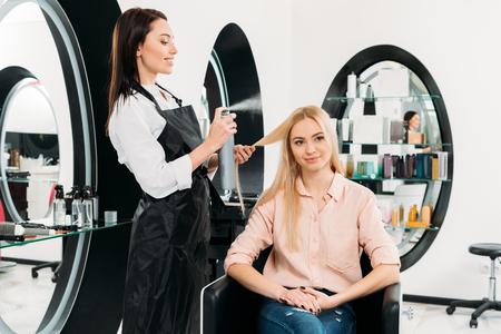 smiling hairdresser applying hair spray 写真素材